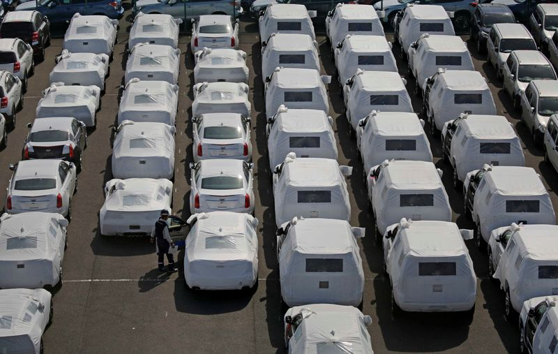 A man works among imported cars covered with a white cloth in a port in Yokohama
