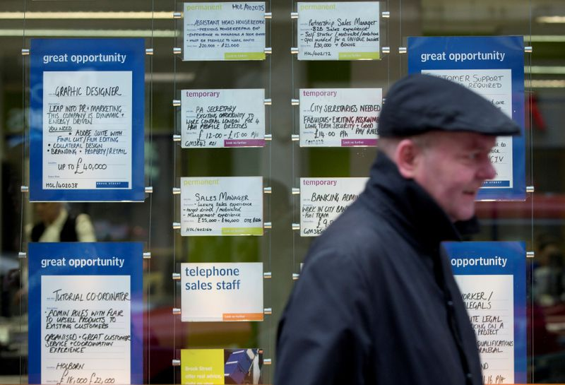 FILE PHOTO:  A man walks past job advertisements in the window of a recruitment office in central London