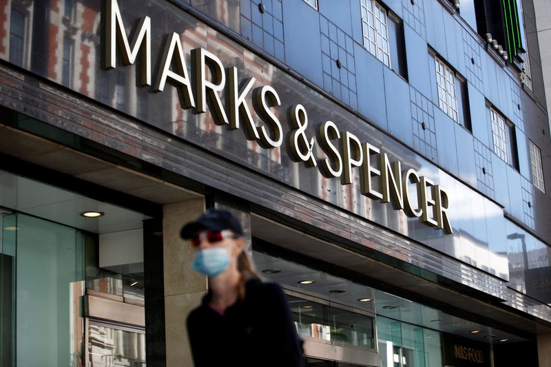 FILE PHOTO: A woman walks past a M&S store at Oxford Street in London, Britain