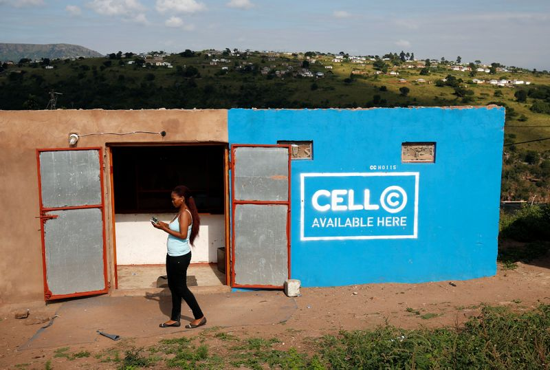 A woman uses her mobile phone in front of a store with telecom company Cell C branding in Kwandengezi
