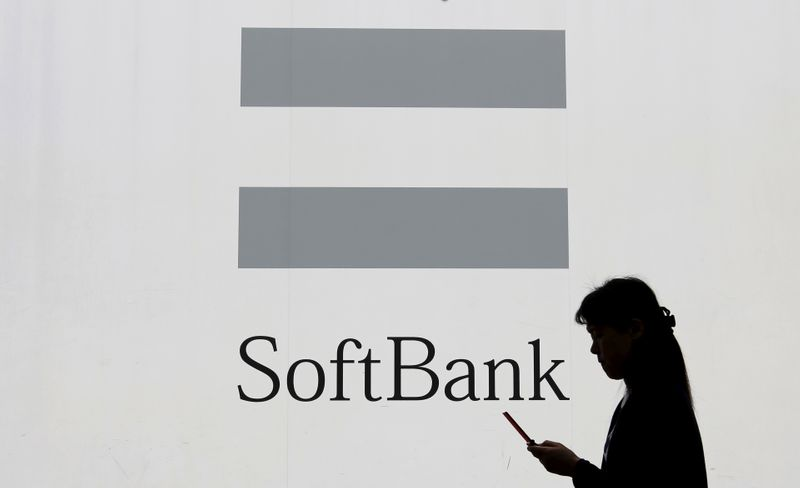 FILE PHOTO: A woman using a mobile phone walks past the logo of SoftBank Corp in Tokyo