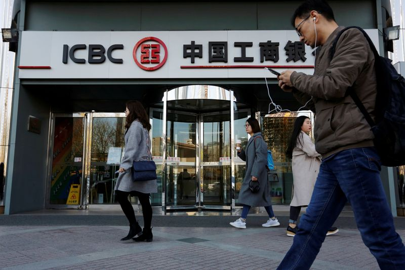 FILE PHOTO: People walk past a branch of Industrial and Commercial Bank of China (ICBC) in Beijing