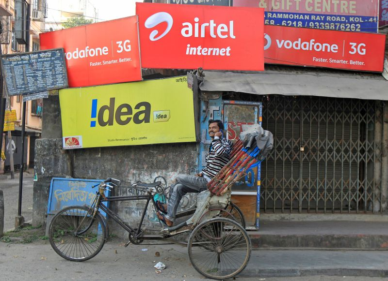 FILE PHOTO: A rickshaw puller speaks on his mobile phone as he waits for customers in front of advertisement billboards belonging to telecom companies in Kolkata