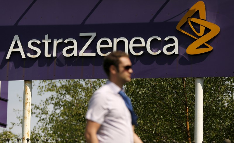 FILE PHOTO: A man walks past a sign at an AstraZeneca site in Macclesfield