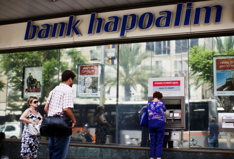 FILE PHOTO: A woman uses an automated teller machine (ATM) outside a Bank Hapoalim branch in Tel Aviv, Israel