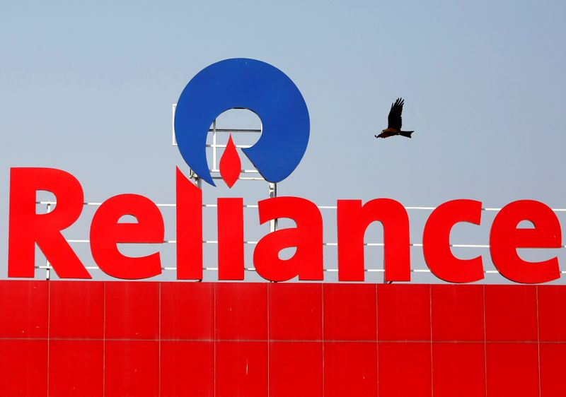 FILE PHOTO: A bird flies past a Reliance Industries sign in Ahmedabad, India