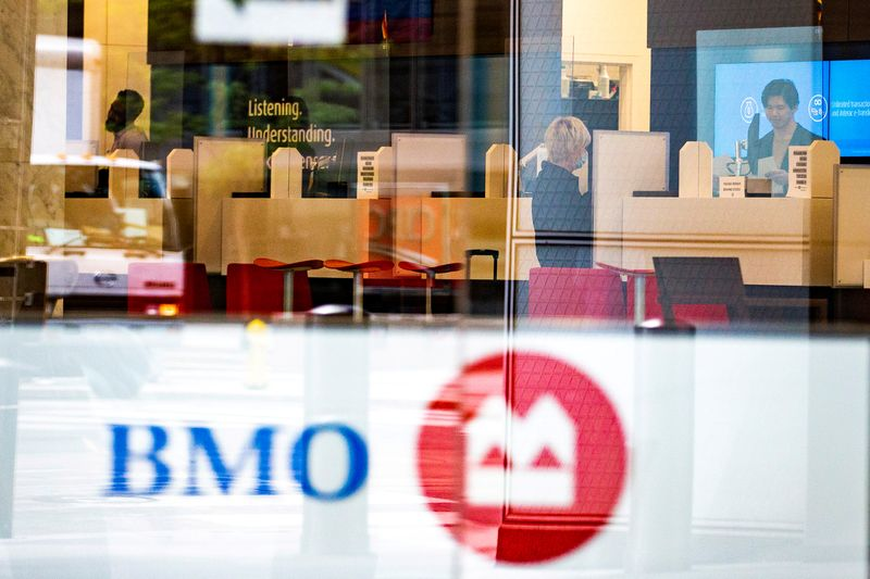 FILE PHOTO: A woman speaks with a bank teller at Bank of Montreal in the financial district of Toronto