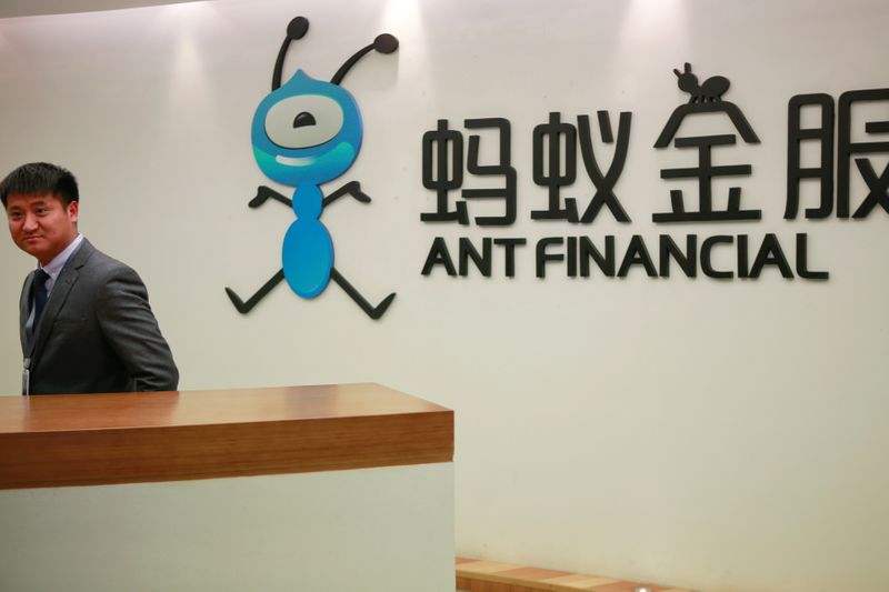 FILE PHOTO: FILE PHOTO: Employee stands next to the logo of Ant Financial Services Group at its headquarters in Hangzhou, China