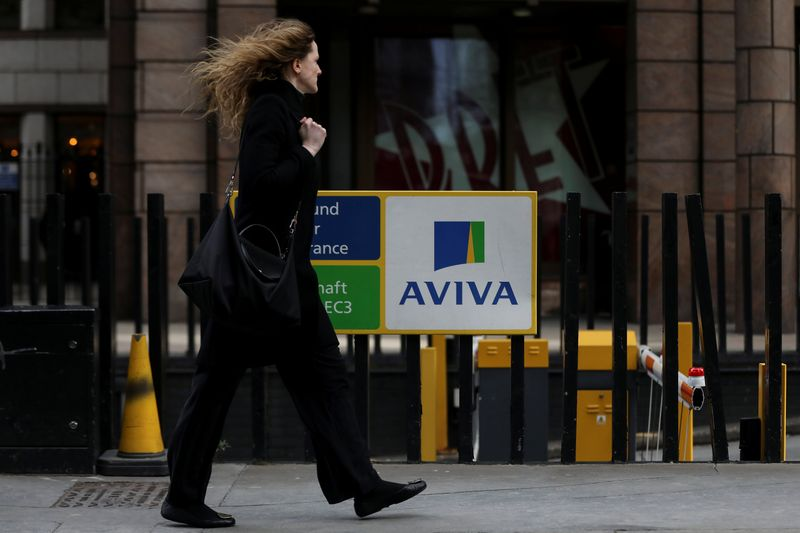 FILE PHOTO: A pedestrians walks past the Aviva logo outside the company head office in the city of London