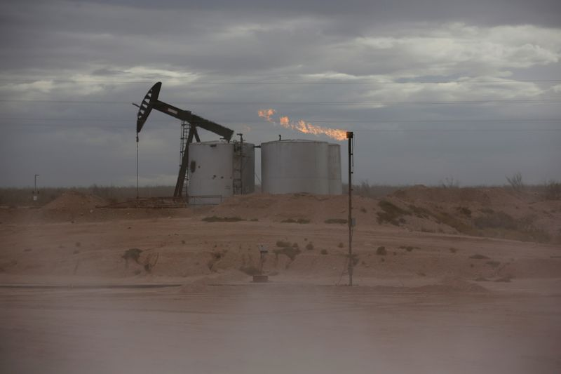 FILE PHOTO: Dust blows around a crude oil pump jack and flare burning excess gas at a drill pad in the Permian Basin in Loving County