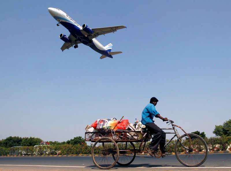 An IndiGo Airlines aircraft prepares to land as a man paddles his cycle rickshaw in Ahmedabad
