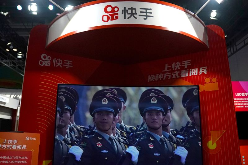FILE PHOTO: A screen showing footage of a military parade is seen at a booth of Chinese video-streaming startup Kuaishou at the 2020 China International Fair for Trade in Services