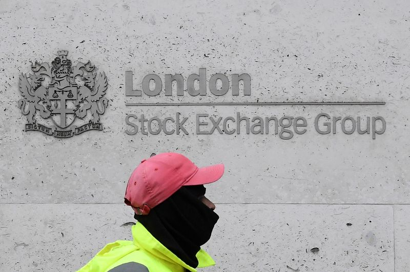 FILE PHOTO: A street cleaning operative walks past the London Stock Exchange Group building in the City of London financial district, whilst British stocks tumble as investors fear that the coronavirus outbreak could stall the global economy, in Lond