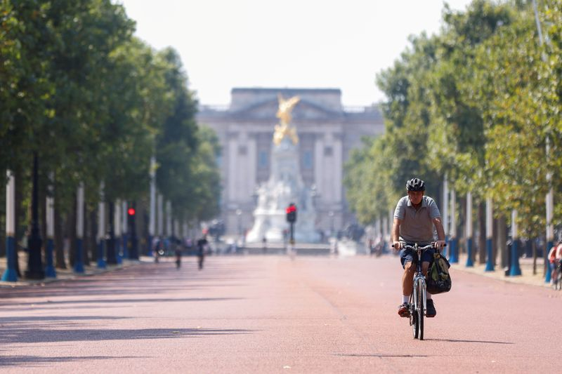 FILE PHOTO: A man cycles down The Mall, with Buckingham Palace in the background, in London