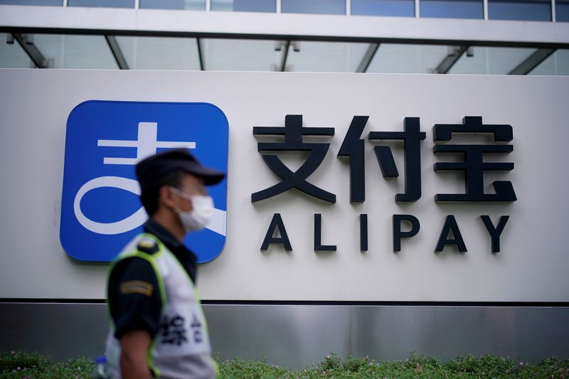 FILE PHOTO: A security guard walks past an Alipay logo at the Shanghai office of Alipay, owned by Ant Group which is an affiliate of Chinese e-commerce giant Alibaba, in Shanghai