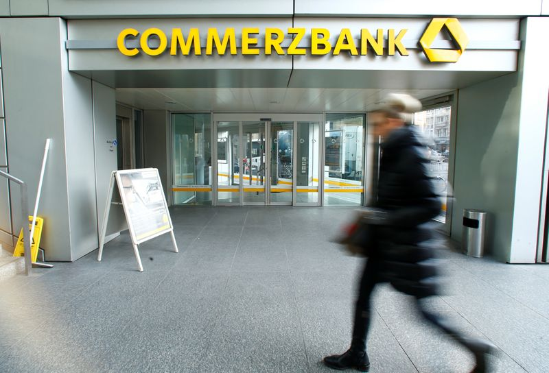 A woman walks past a branch of Commerzbank before the bank's annual news conference in Frankfurt