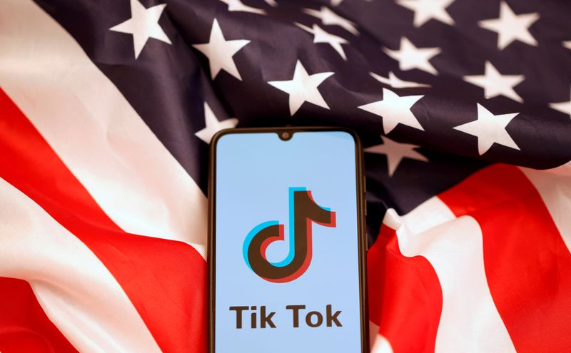 FILE PHOTO: TikTok's logo is displayed on the smartphone while standing on the U.S. flag in this illustration