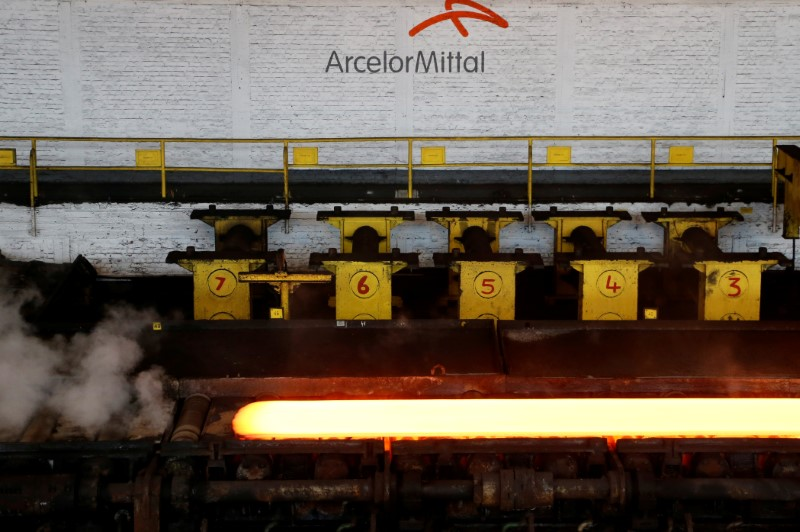 FILE PHOTO: A red-hot steel plate passes through a press at the ArcelorMittal steel plant in Ghent