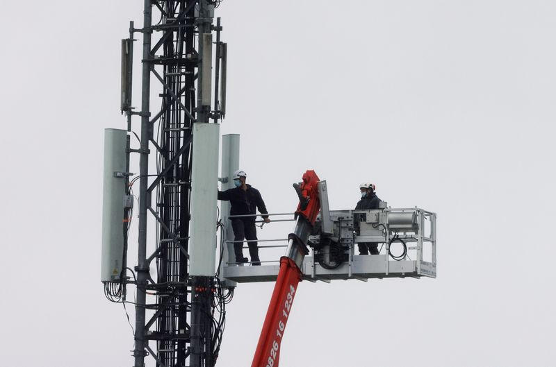 FILE PHOTO: Technicians work at the top of transmitting antennas are seen on a mobile-phone network relay mast in Lambres-lez-Douai