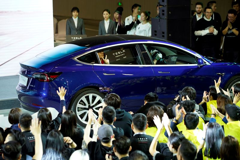 FILE PHOTO: Tesla China-made Model 3 vehicle owner sits inside a car during a delivery event at Tesla's Shanghai factory