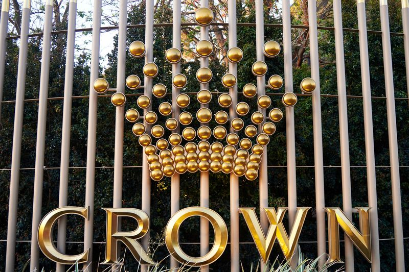 FILE PHOTO: The logo of Australia's top casino operator Crown Resorts adorns a fence surrounding the Crown Perth hotel and casino complex in Western Australia
