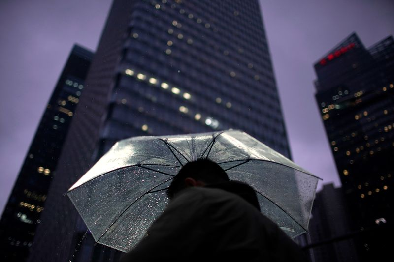 FILE PHOTO: A man walks with an umbrella in Lujiazui financial district in Pudong