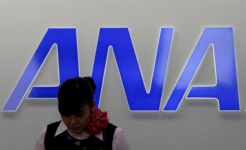 FILE PHOTO: An employee of All Nippon Airways works in front of the company logo at New Chitose airport in Chitose