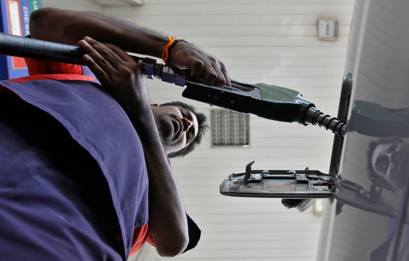 A worker fills diesel in a vehicle at a fuel station in Chennai