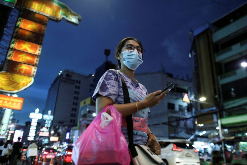 FILE PHOTO: A woman wearing a protective face mask walks on a street in Bangkok, Thailand