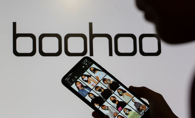 A woman poses with a smartphone showing the Boohoo app in front of the Boohoo logo on display in this illustration