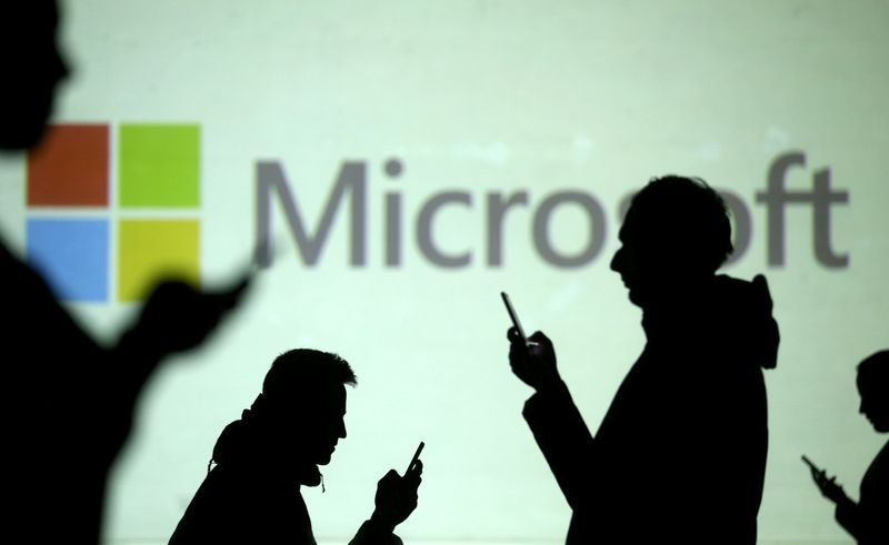 FILE PHOTO: FILE PHOTO: Silhouettes of mobile users are seen next to a screen projection of Microsoft logo in this picture illustration