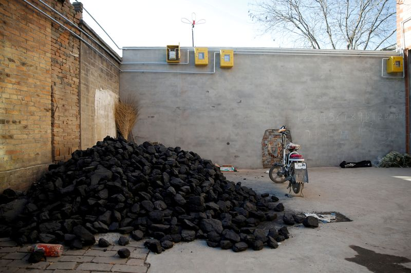 FILE PHOTO: A pile of coal is seen underneath newly installed gas pipes in a courtyard in the village of Heqiaoxiang