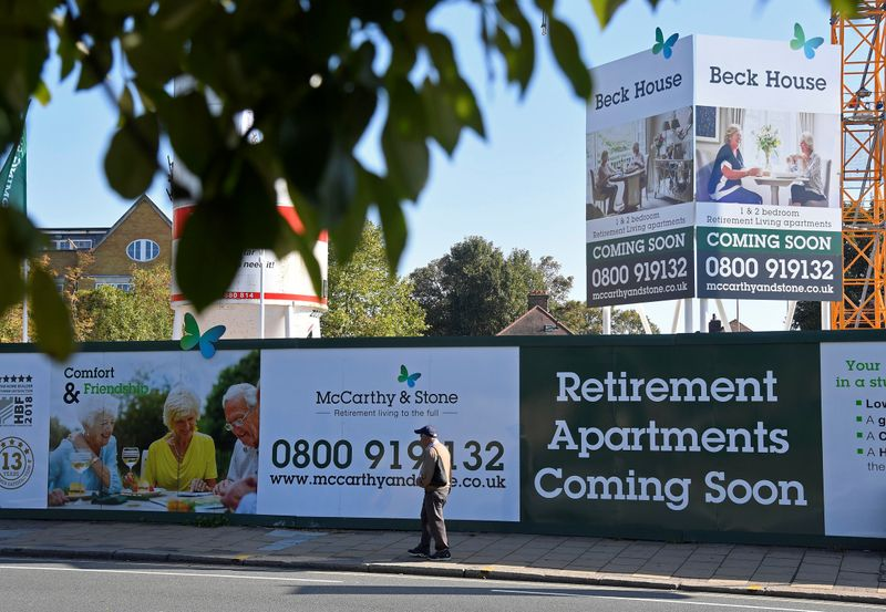 FILE PHOTO:  A man walks past hoardings advertising retirement apartments currently being built behind on site by McCarthy & Stone in London, Britain