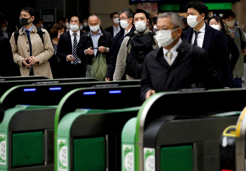 FILE PHOTO: Passengers wearing protective face masks, following an outbreak of the coronavirus disease, are seen at a station after the government announced the state of emergency for the capital following the disease outbreak in Tokyo, Japan