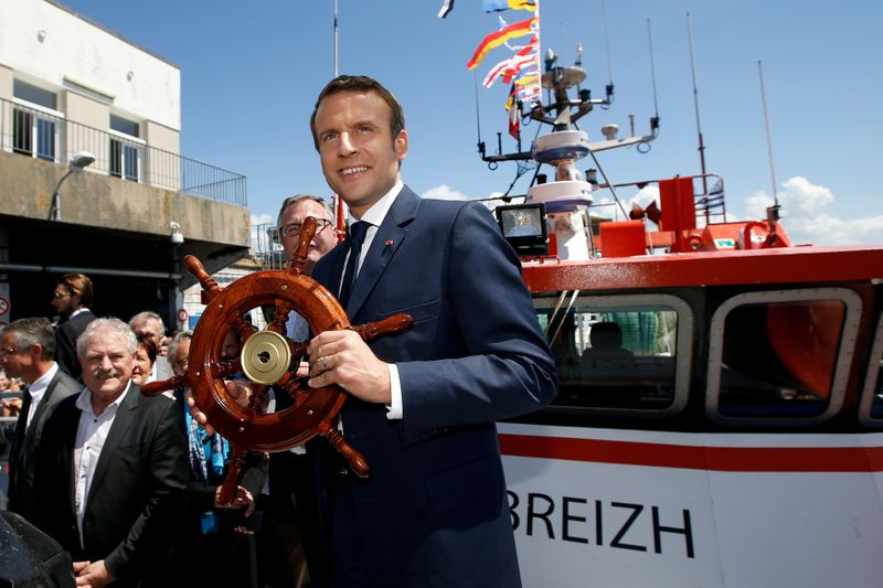 FILE PHOTO: French President Emmanuel Macron receives a gift on a trawler as he visits the harbour of Lorient