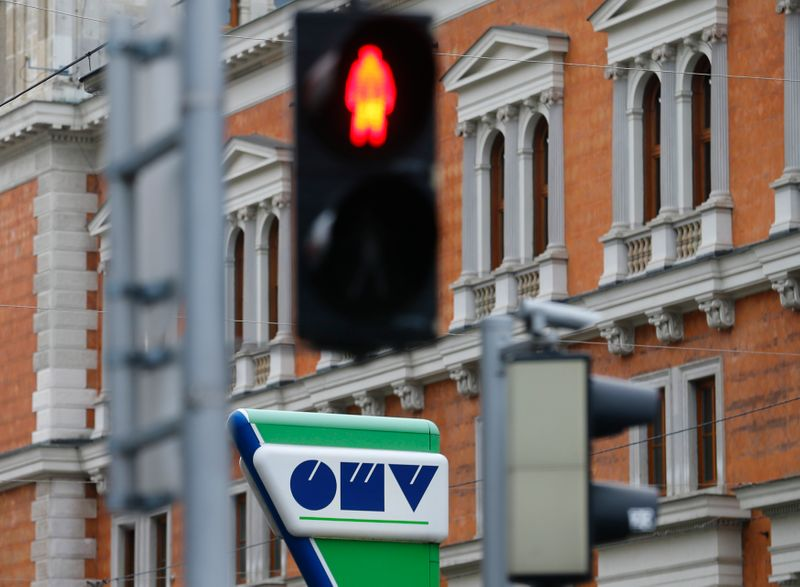 The logo of Austrian energy group OMV is pictured behind traffic lights at a gas station in Vienna