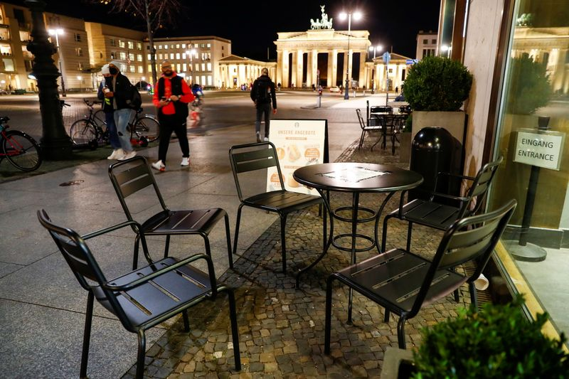 People walk by empty tables of a cafe in front of the Brandenburg Gate, in Berlin