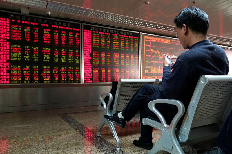 FILE PHOTO: An investor uses his mobile phone in front of a stock quotation board at a brokerage office in Beijing