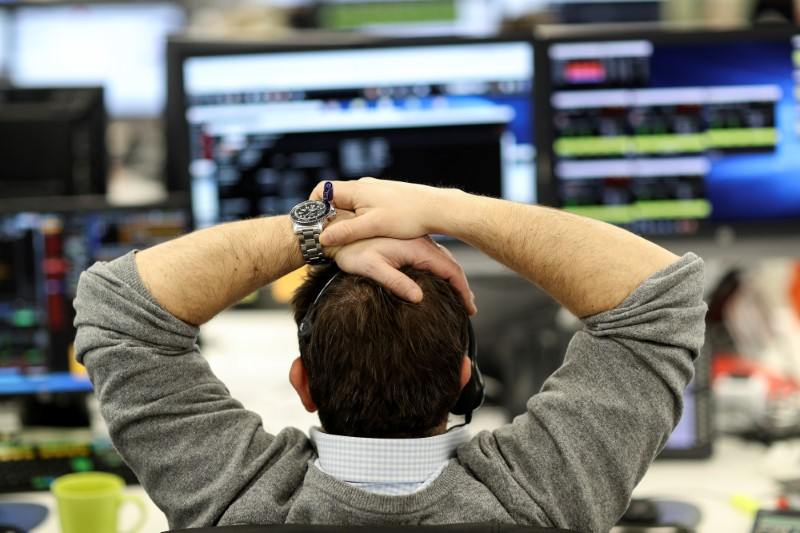 FILE PHOTO:  A broker looks at financial information on computer screens on the IG Index trading floor