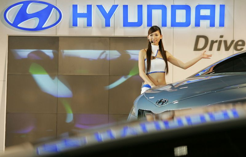 FILE PHOTO: A model poses next to new Hyundai cars during the 16th Taipei International Auto Show December 23, 2..