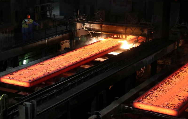 FILE PHOTO: Red-hot steel plates pass through a press at the Tata steel plant in Ijmuiden