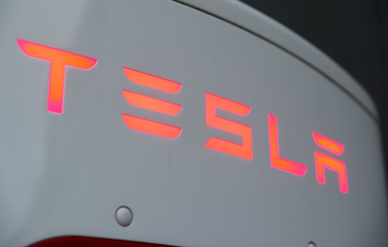 The logo of Tesla is seen at a Tesla Supercharger station in Dietikon
