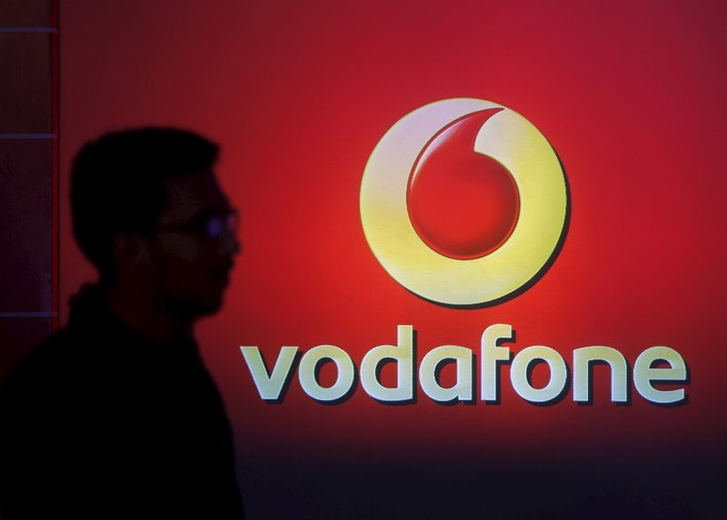 A man casts silhouette onto an electronic screen displaying logo of Vodafone India after a news conference to announce the half year results in Mumbai