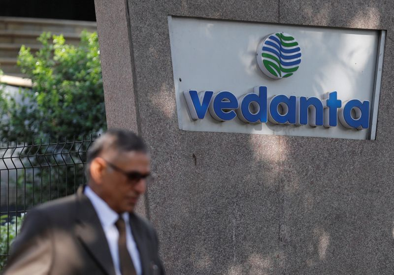 FILE PHOTO: A man walks past the logo of Vedanta outside its headquarters in Mumbai