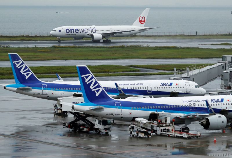 FILE PHOTO: A Japan Airlines (JAL) aircraft takes off near All Nippon Airways (ANA) aircrafts at Haneda Airport in Tokyo