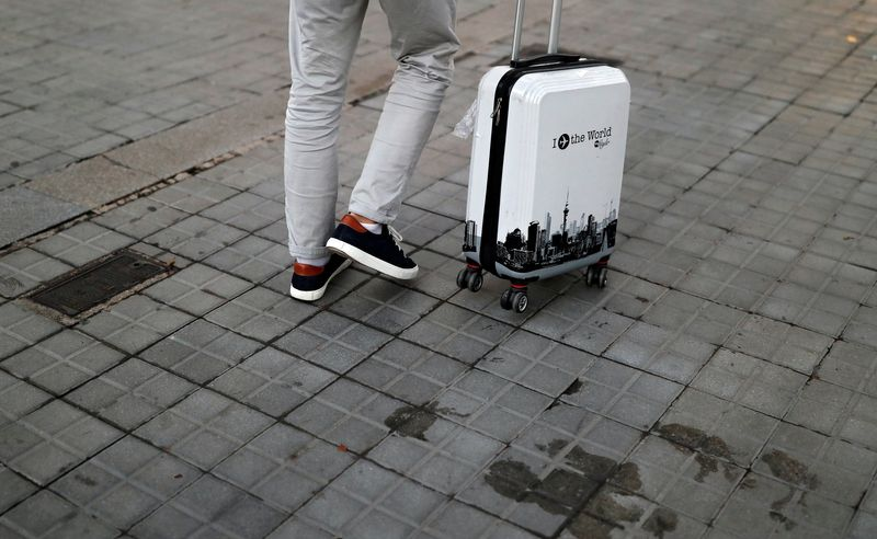 A tourist walks with his suitcase, amid the coronavirus disease outbreak, in Barcelona