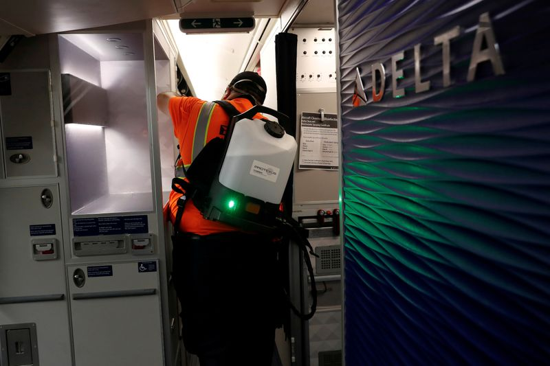 FILE PHOTO: A Delta Air Lines pre-flight cleaning crew member uses an electrostatic disinfection device to clean an aircraft at JFK International Airport in New York