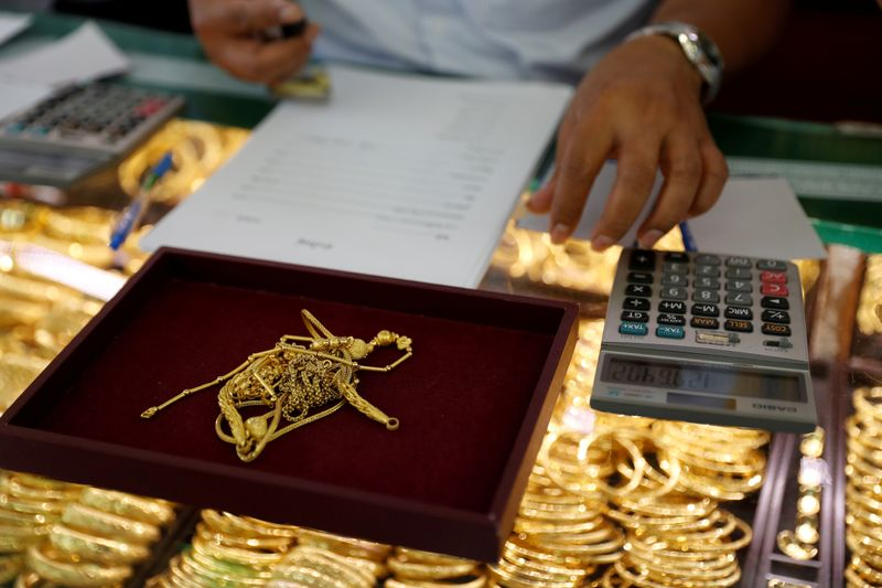 FILE PHOTO: A goldsmith evaluates gold inside a shop in Bangkok, Thailand