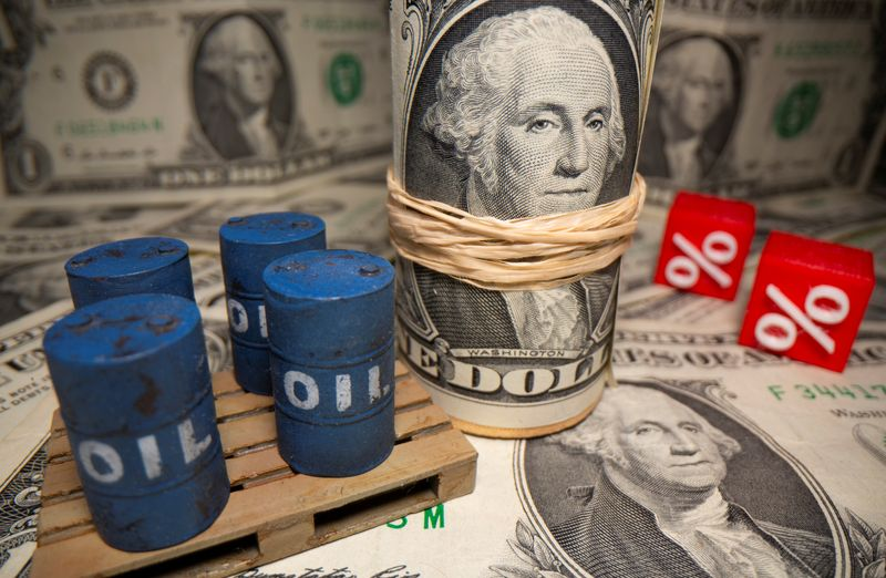 3D printed oil barrels and percentage symbols are seen in front of dollar banknotes in this illustration