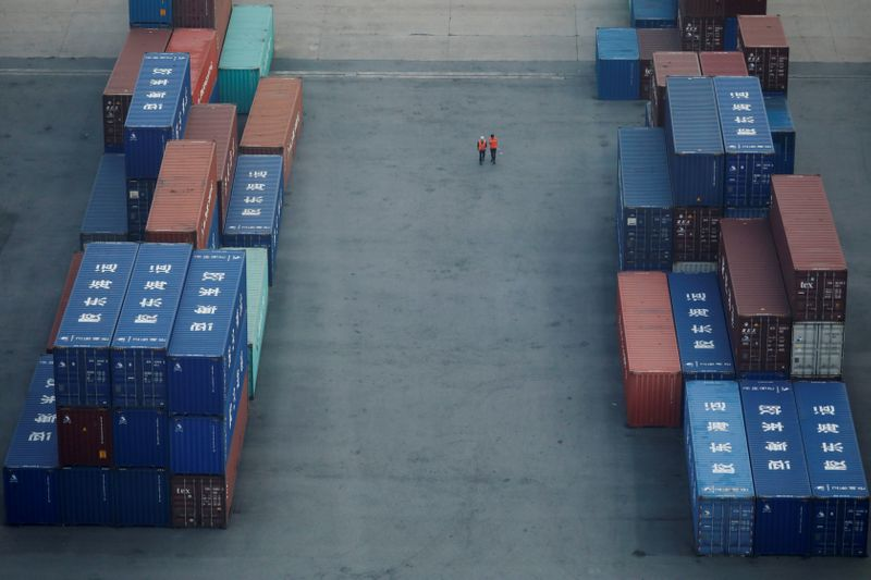 Workers walk past shipping containers at Pyeongtaek port in Pyeongtaek